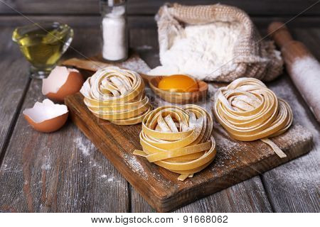 Raw homemade pasta and ingredients for pasta on wooden background