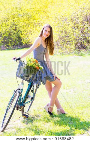 Young woman in short grey dress with long hair rides a bicycle with basket and flowers tour summer city park, look and smile on camera