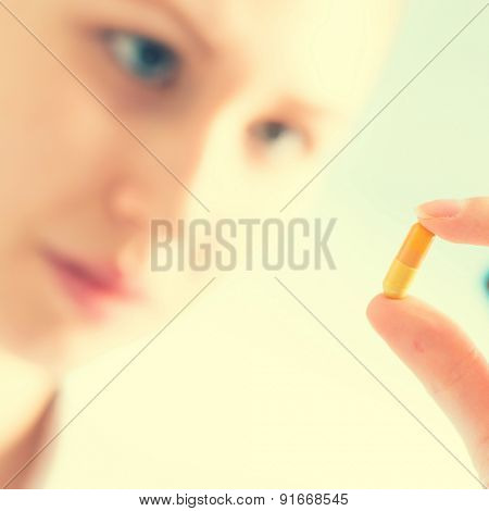 Doctor woman hold medicine capsule, pill in hand. Toned photo
