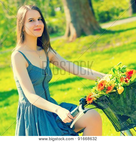Young woman in short grey dress with long hair rides a bicycle with basket and flowers tour summer city park, look and smile on flowers bouquet. Toned photo