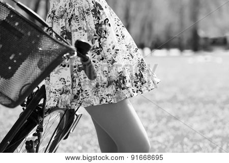 girl in short dress with bike in summer park, black and white photo