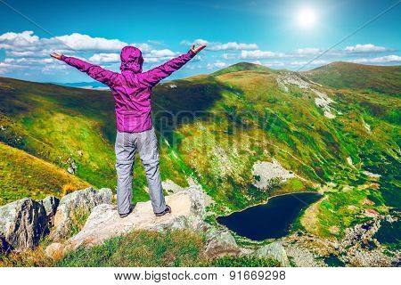 Woman standing with raised hands on top of a mountain. Carpathians, Ukraine