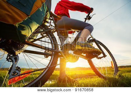 Hiker with loaded bicycle on a green summer meadow at sunset