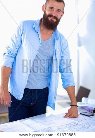Portrait of male designer sitting on a table with blueprints.