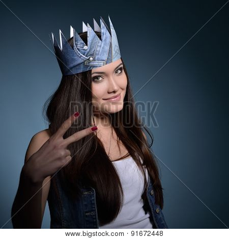 Pretty jeans princess. Beautiful girl in jeans and paper crown over blue background.