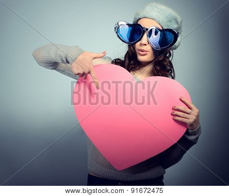 Cute attractive fashion young girl posing with funny big love glasses and pointing at pink heart