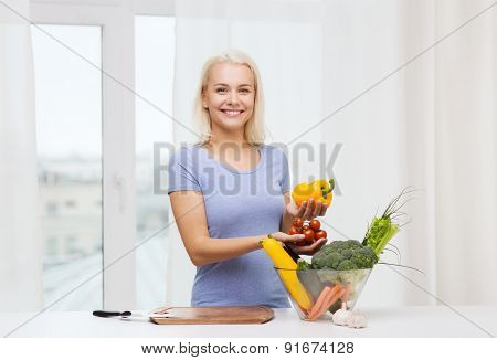 healthy eating, cooking, vegetarian food, dieting and people concept - smiling young woman with bowl of vegetables at home