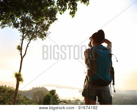 woman photographer taking photo at mountain peak