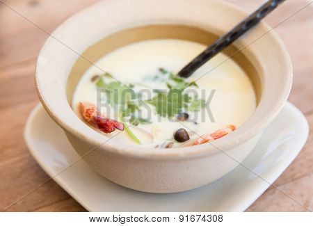 cooking, asian kitchen and food concept - bowl of creamy soup with shrimps and spoon on wooden table