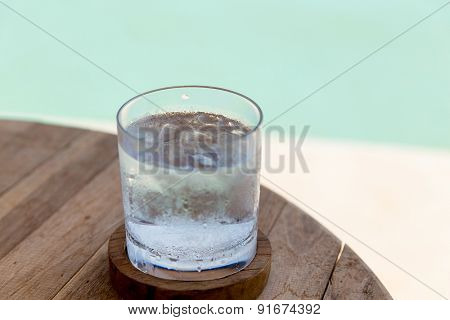 travel, tourism, drinks and refreshment concept - glass of cold water with ice cubes on table at beach