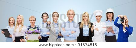 people, profession, qualification, employment and success concept - happy businesswoman with group of professional workers over blue background