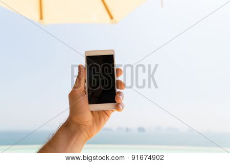 technology, travel, tourism, communication and people concept - close up of male hand holding smartphone with blank screen on summer beach