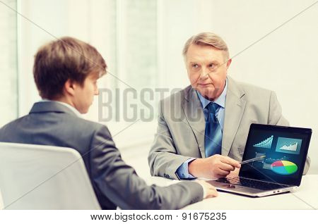 business, advertisement, technology and office concept - older man and young man with laptop computer in office