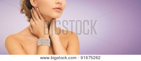 beauty, people and jewelry concept - close up of beautiful woman with pearl earrings and bracelet over violet background