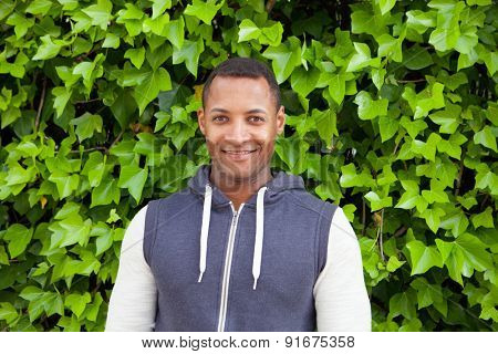 Afroamerican guy on a park with a plants of background