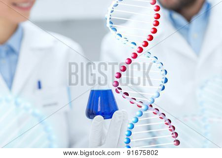 science, chemistry, biology, medicine and people concept - close up of scientists with test tube or glass flask making test or research in clinical laboratory