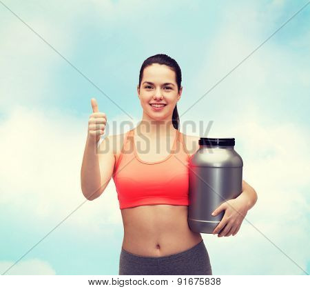 fitness and diet concept - smiling teenage girl with jar of protein showing thumbs up