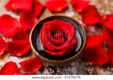 roses petals in bowl with pile of salt on old wooden board