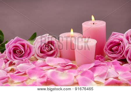 Pink rose with three pink candle and petals on mat