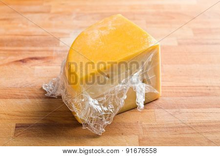 wrapped edam cheese on kitchen table