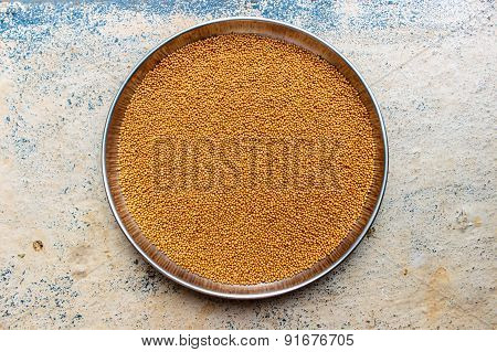 Raw yellow coloured mustard seeds kept in a plate for drying under the sunlight