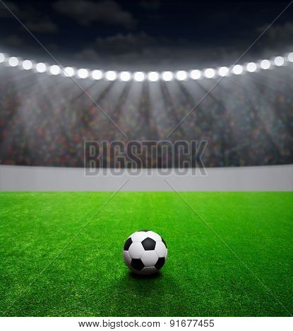Soccer ball on green stadium, arena in night illuminated bright spotlights