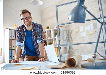 Happy young employee standing by workplace in office