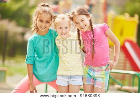 Active friends in casualwear looking at camera outdoors