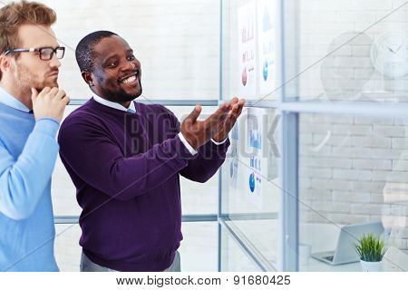 Confident managers comparing financial reports in office
