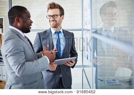 Two confident colleagues sharing ideas at meeting in office
