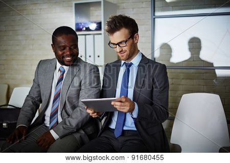 Two male colleagues looking through data in office