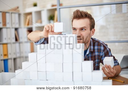 Creative businessman in casualwear building paper pyramid