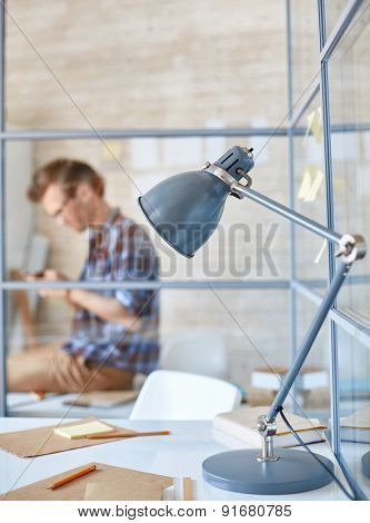 Workplace with lamp, papers and pencils with sitting businessman on background