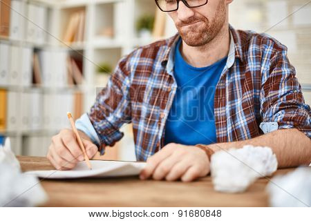 Young businessman with pencil writing down his ideas with crumpled sheets near by