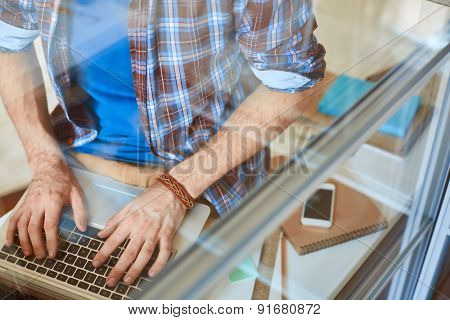 Young businessman hands pushing laptop keys