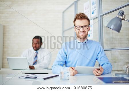 Young man with touchpad looking at camera at workplace