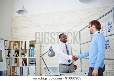 Young employer congratulating newly hired man