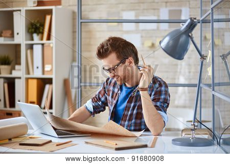 Young businessman learning draft at workplace