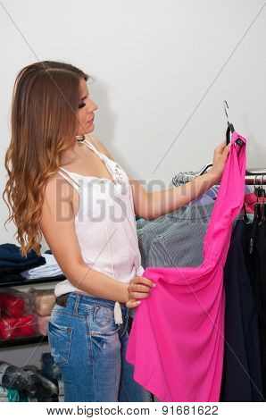 Beautiful teenage girl looking pink dress in a boutique