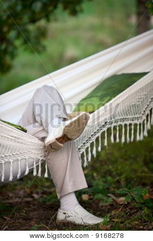 Man In Light Suit In Fabric Hammock