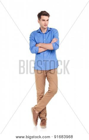 Full body picture of a casual young man standing with his hands crossed on idolated background.