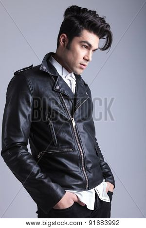 Side view of a young fashion man holding his hands in pockets while looking away from the camera.