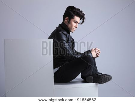 Side view of a fashion man sitting on a while furniture while looking away from the camera with his hands together.