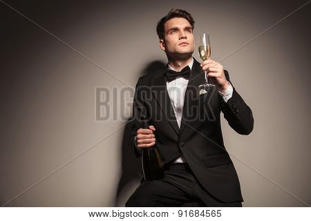 Young elegant business man enjoying a glass of champagne while siting on a chair.