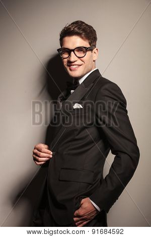 Smiling young business man holding one hand in his pocket.