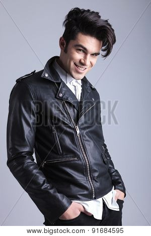 Portrait of a smiling young man looking at the camera while holding his hands in pockets.