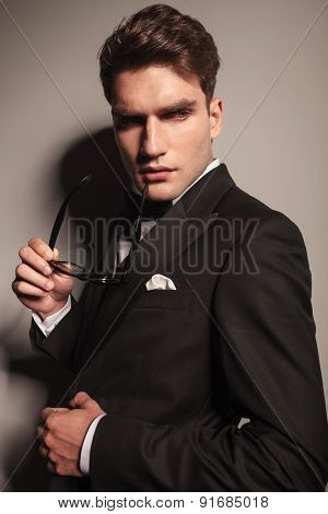 Side view portrait of a elegant young business man holding a pair of glasses in his hand.