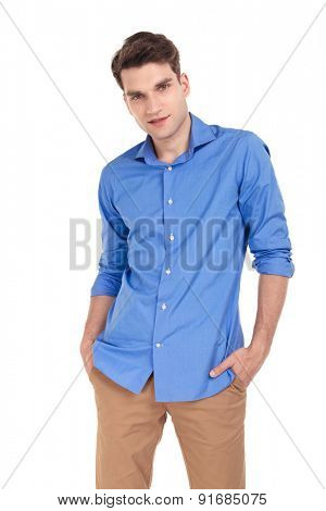 Handsome young man posing with his hands in pockets on isolated background.