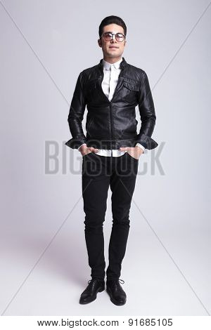 Full body picture of a handsome fashion man standing on studio background with his hands in pockets.
