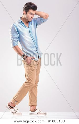 Young casual man walking on grey studio background fixing his hair while holding one hand in his pocket.